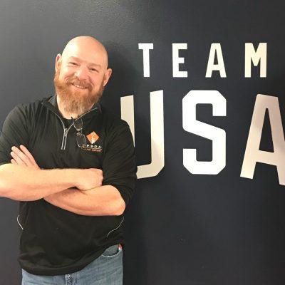 Man standing next to Team USA sign