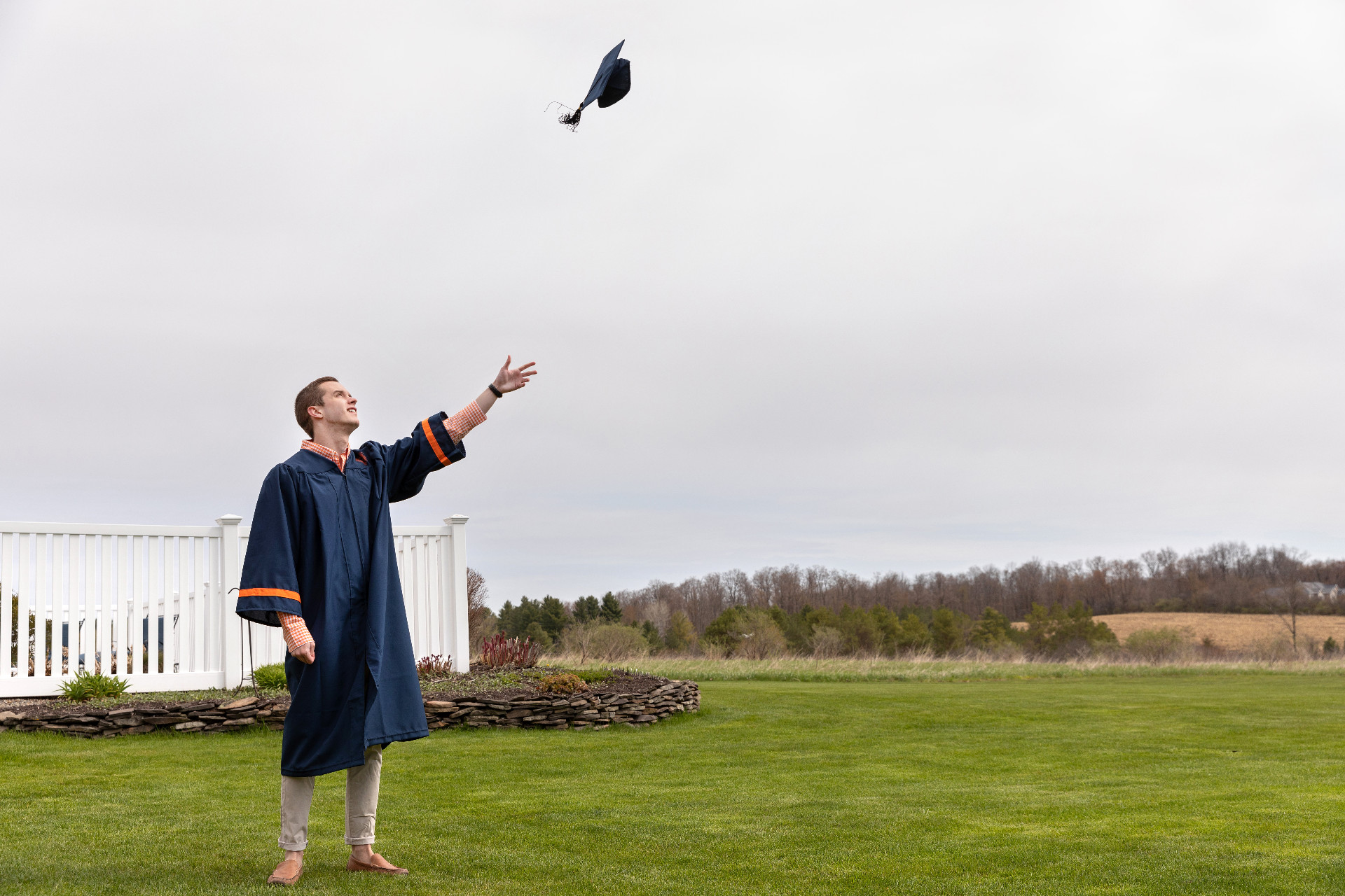person throwing graduation cap in air