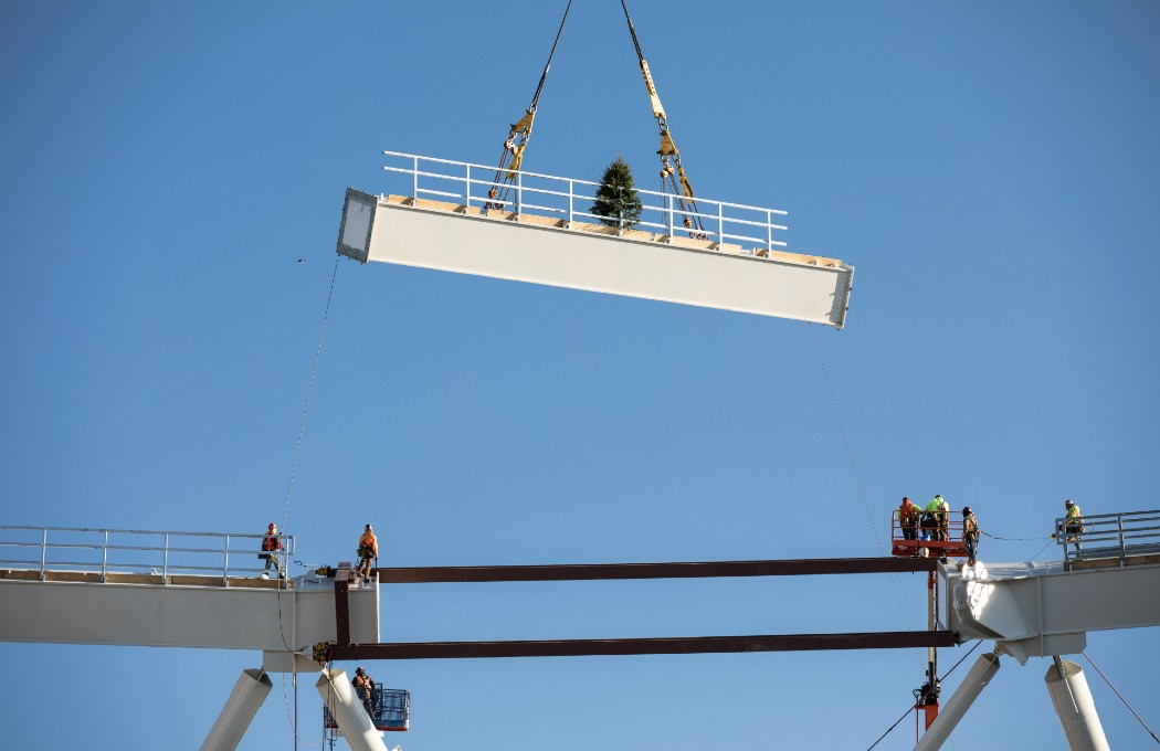 steel beam being lowered into stadium roof crown-truss