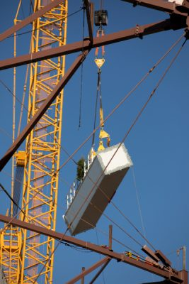 steel beam being lowered by crane