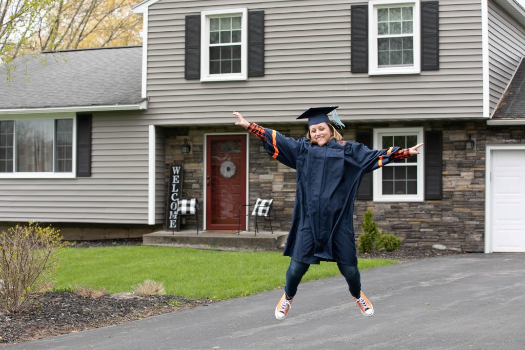 person in graduation gown jumping in driveway