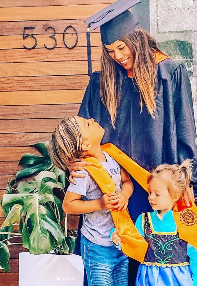 person in graduation gown with two children