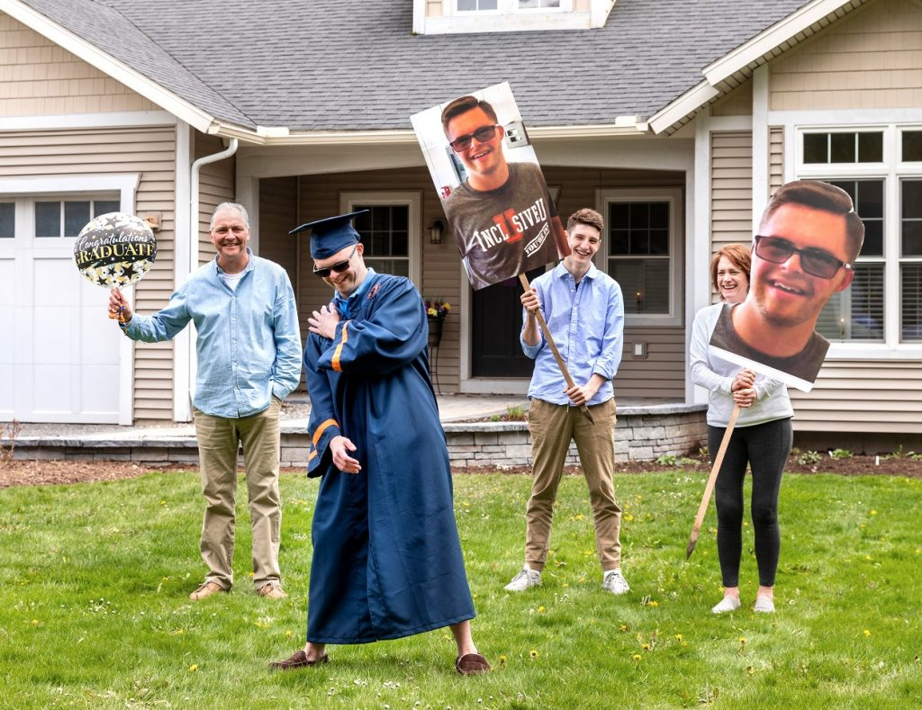 graduate standing in front yard with family members