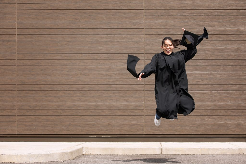 person in graduation gown jumpin