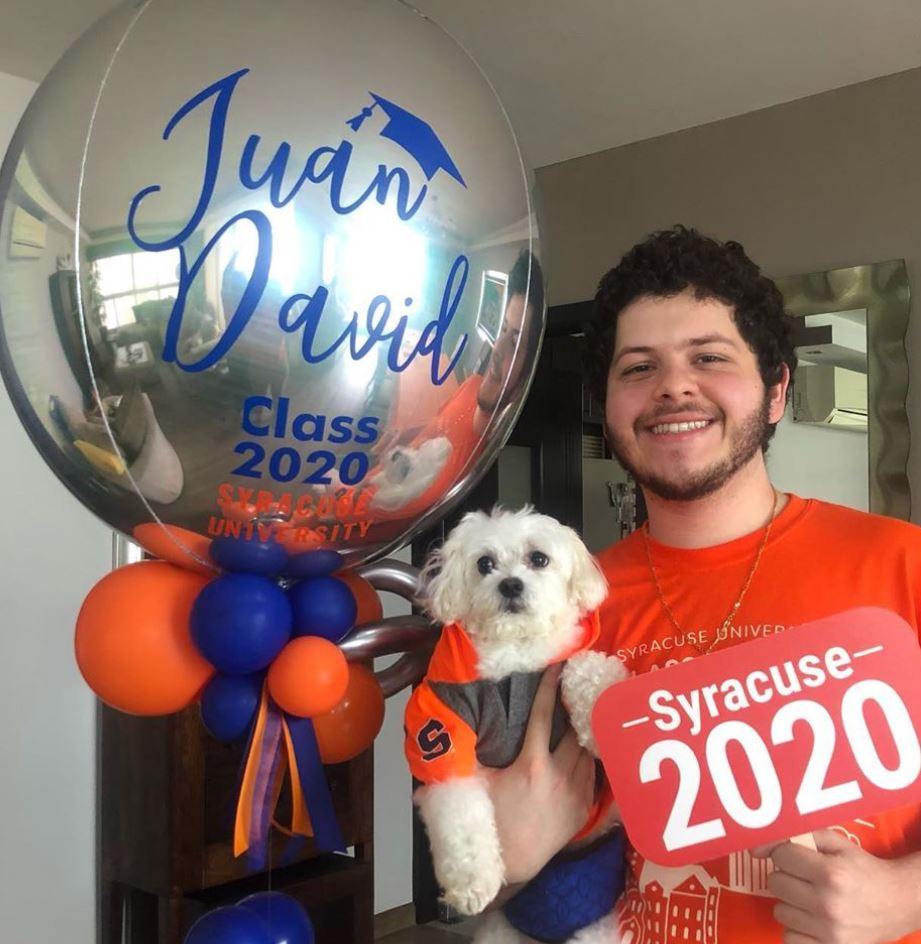 person holding dog, ballons and Syracuse University decorations