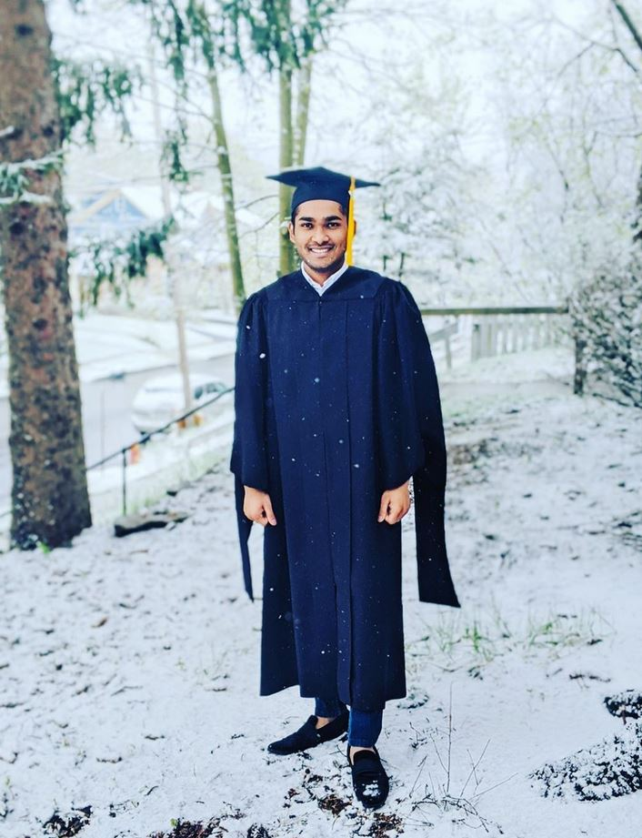 person in graduation gown on snowy yard