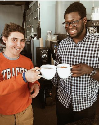 Two students holding coffee mugs