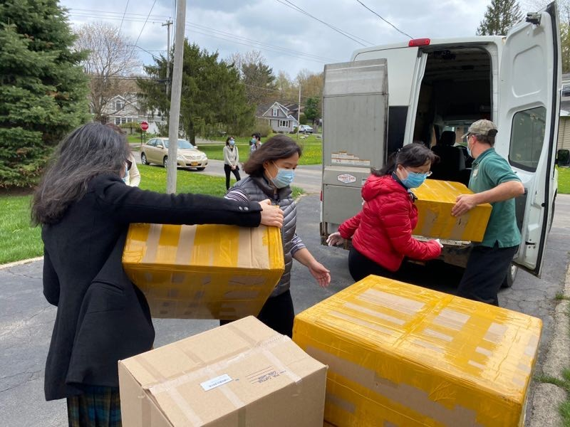 people loading boxes in vehicle