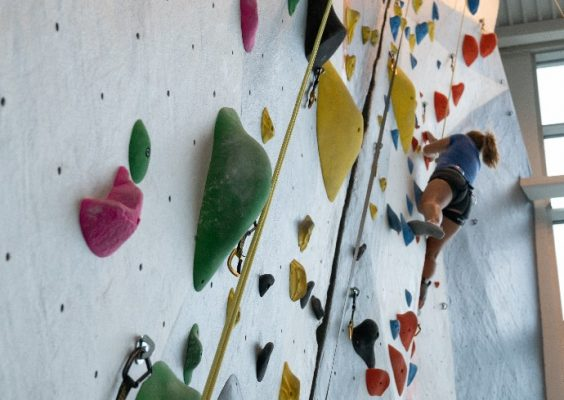 person utilizing rock climbing wall at the Barnes Center at The Arch