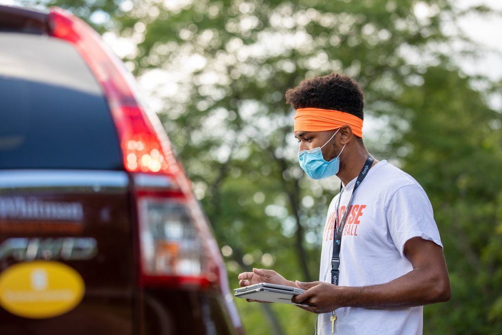 person in mask speaking with person in car