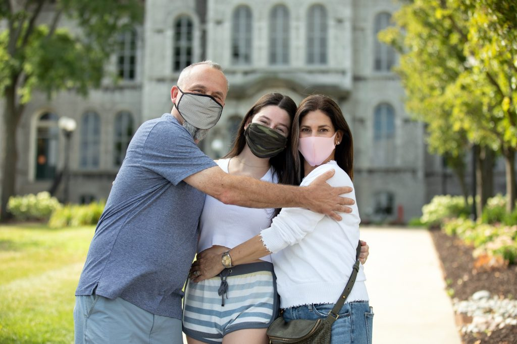 three people with masks hugging