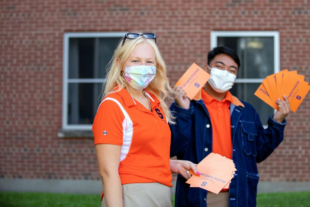 two people with masks holding postcards