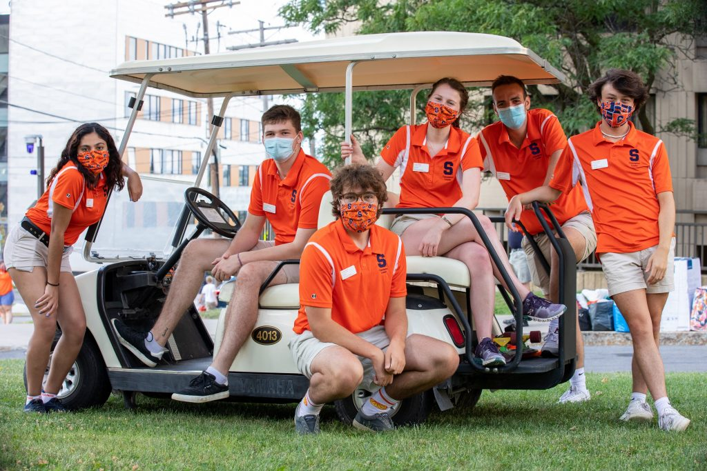 people wearing masks on and next to a golf cart