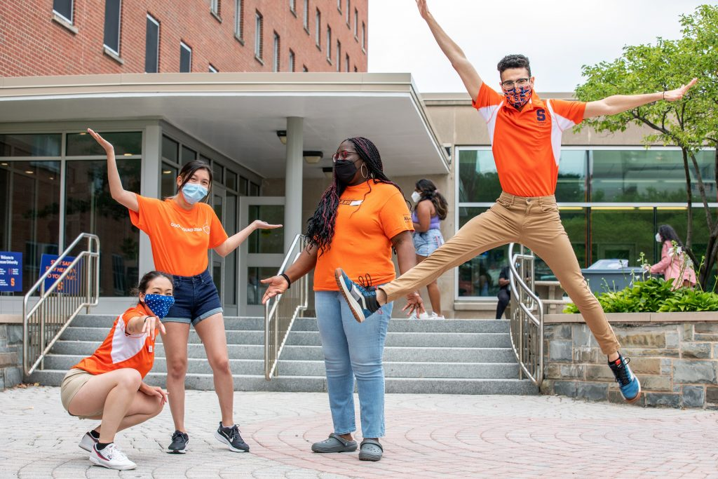 four people posing in front of residence hall