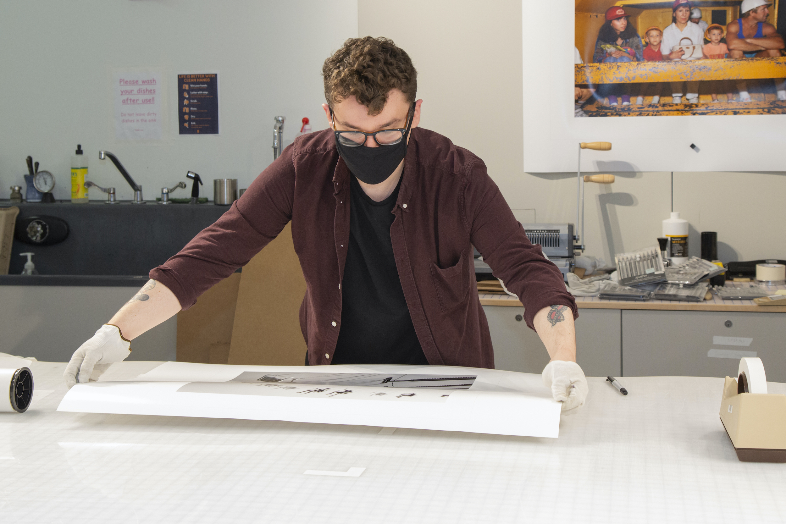 staff member working on large photo at a table