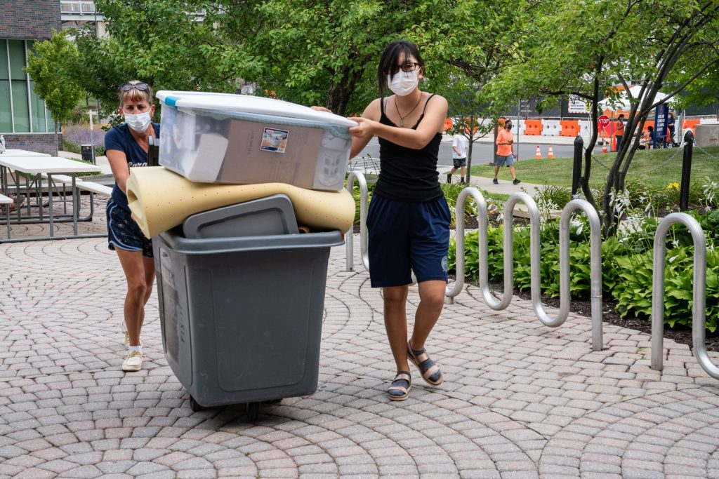 two people pushing bin with belongings