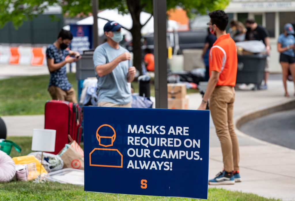 people with masks talking in front of yard sign