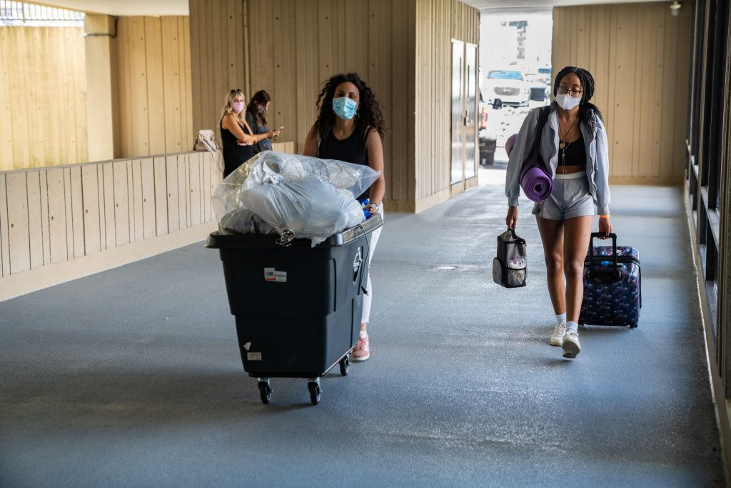 two people with masks pushing bin and carrying belongings into residence hall