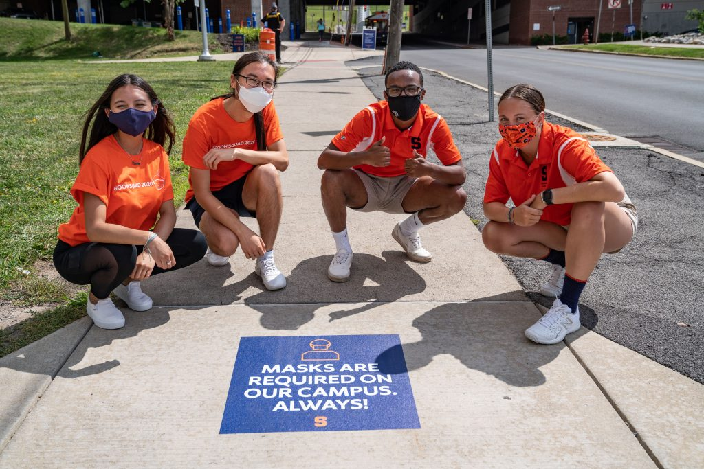people wearing masks next to a decal on the ground