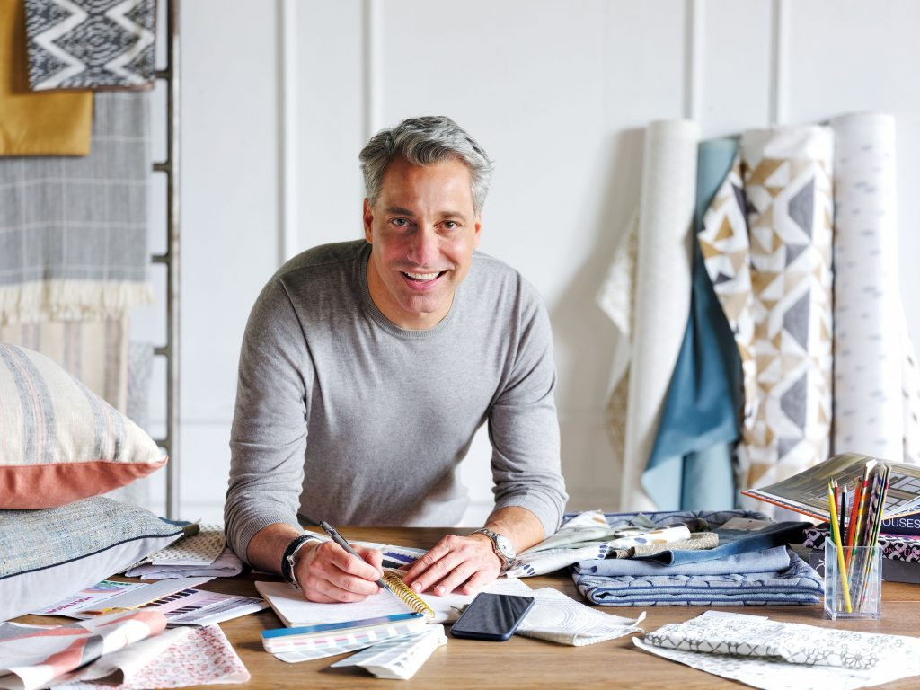 man in workroom with cloth swatches