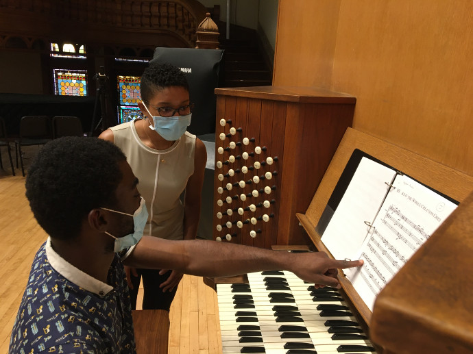 person playing organ while another person watches