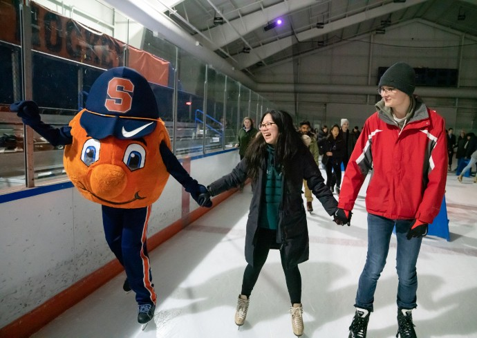 Otto mascot and two students holding hands on ice skating rink