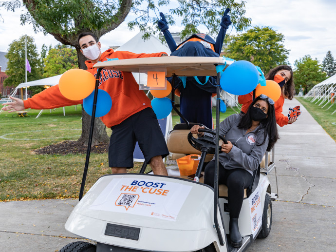 three people and Otto riding around in golf cart on the Quad on Syracuse University campus