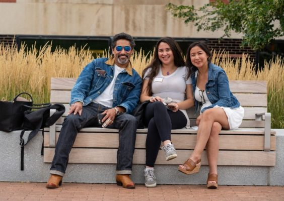 a student and two family members seated on a bench during Family Weekend 2019