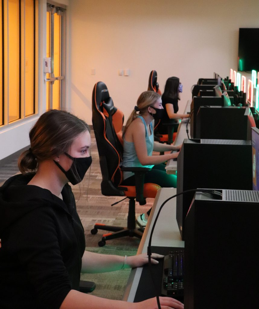 people wearing masks sitting at computers