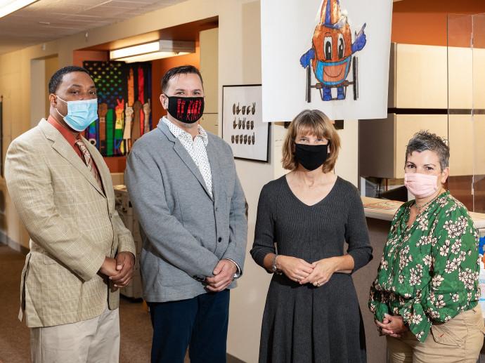 four people standing in corridor wearing masks