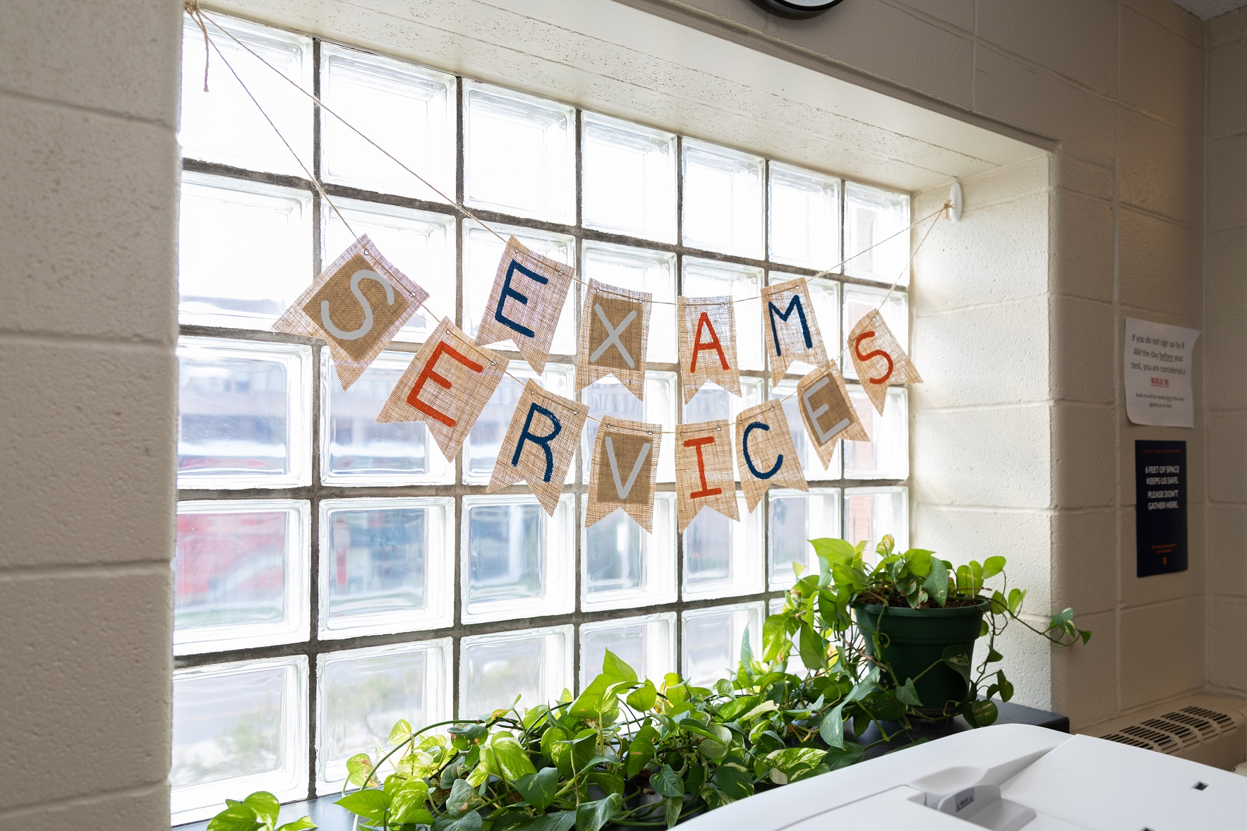 letters in window that spell out Exam Services in office setting