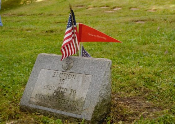 """a memorial headstone that says """"Section 15 Dedicated to Our Nations' Veterans"""" adorned with an American flag and a Syracuse University flag"""