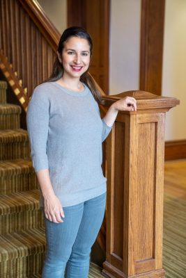 Sarah Workman, director of proposal development, poses near a staircase in the Tolley Humanities Building