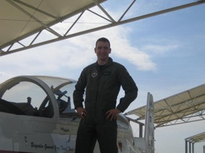 Lt. Col. Travis Sheets posing in front of an aircraft