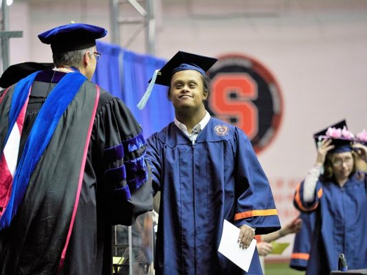 person crossing stage in commencement ceremony