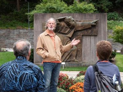 David Prince speaking in front of sculpture