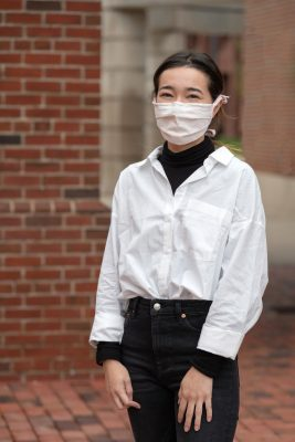 student Taylor Spires poses in a mask in front of a brick wall