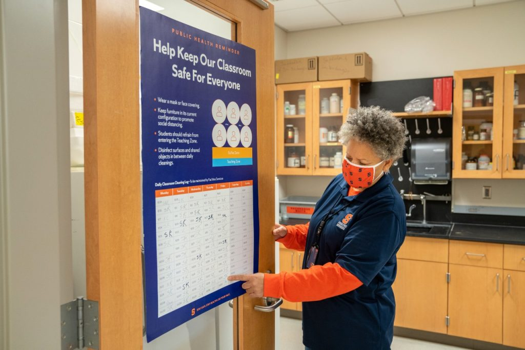 Annette Statum pointing to a classroom poster