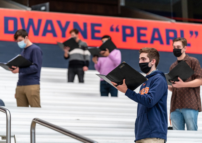 choir members singing in stadium wearing masks