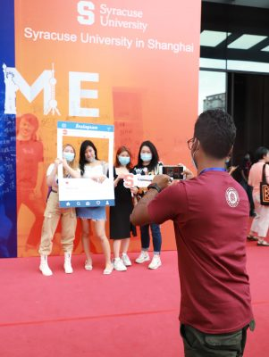 SU students in China posing in front of a Syracuse University sign