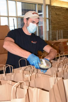 Food Services staff member packing food items into paper bags