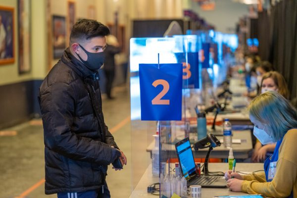 testing assistant helps a student check-in at the Testing Center
