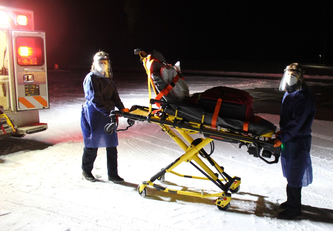 emergency services providers in personal protective equipment (PPE) with stretcher