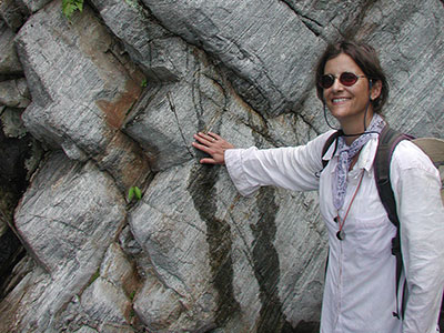 Suzanne Baldwin stands with hand on metamorphic rock in New Guinea