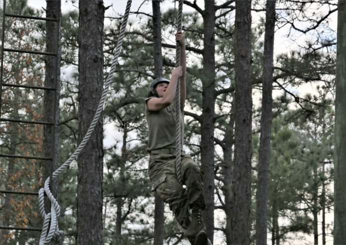 person climbing rope in woods