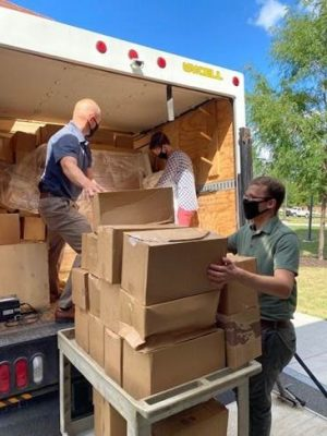 three people in masks unloading boxes from a truck