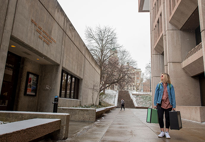 student with luggage looking at campus building