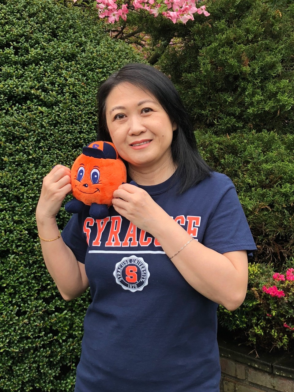 Sui, mom of Amanda Chau, poses in a Syracuse T-shirt with an Otto plush