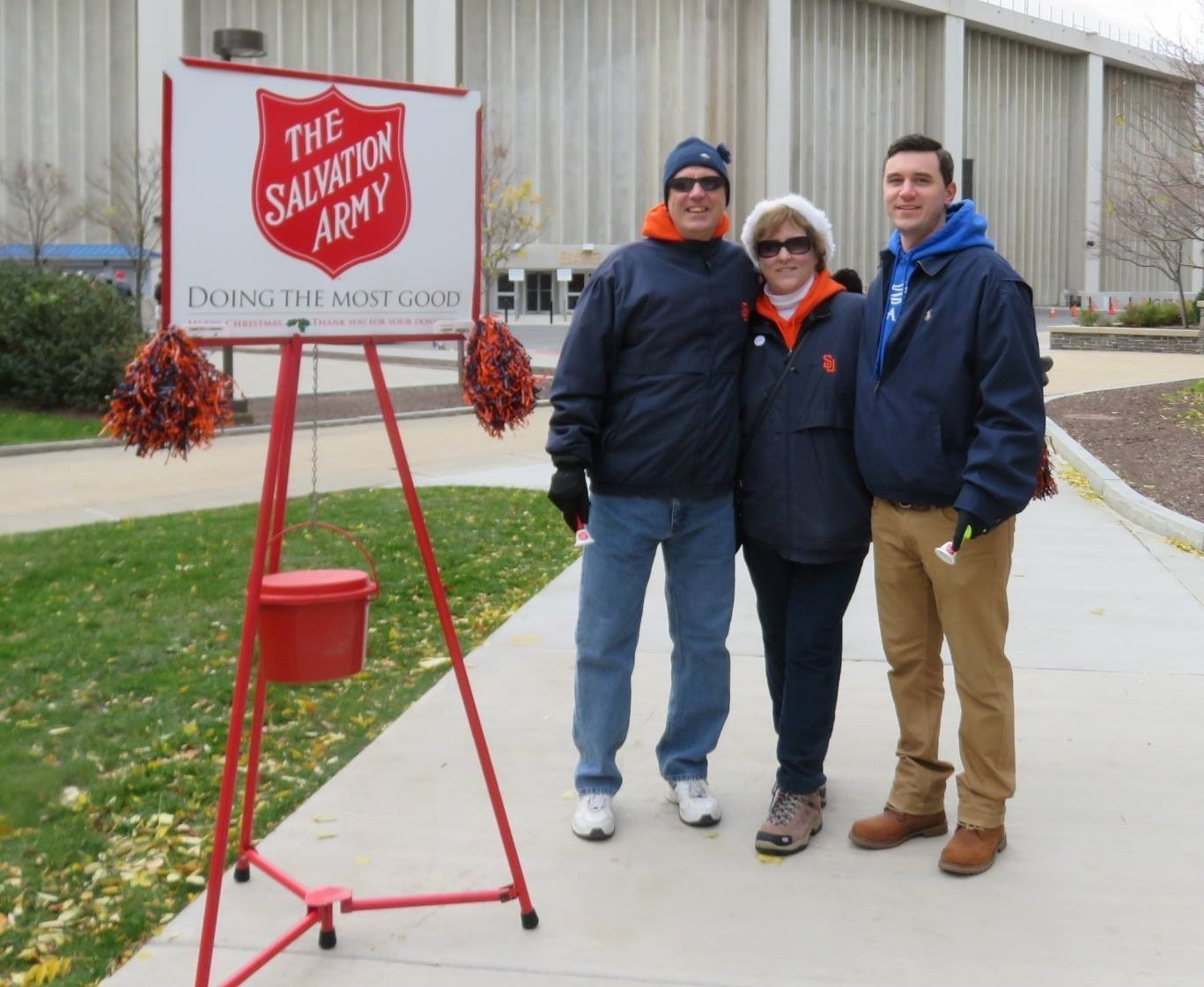 Mark, Joanne and Brian Balduzzi ringing the bell for Salvation Army on campus