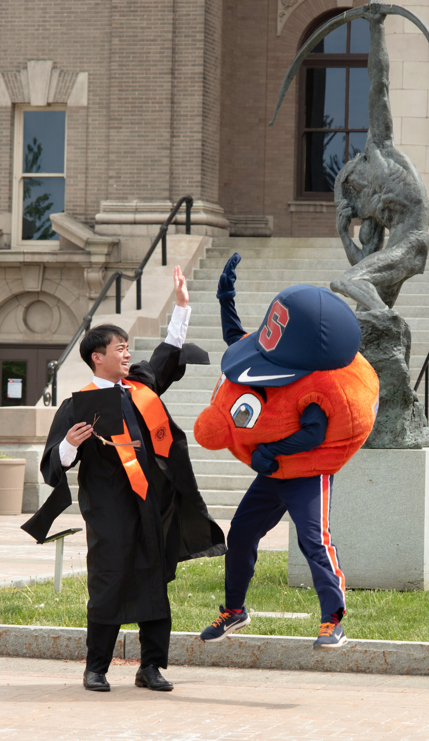 student and Otto high-fiving during Commencement